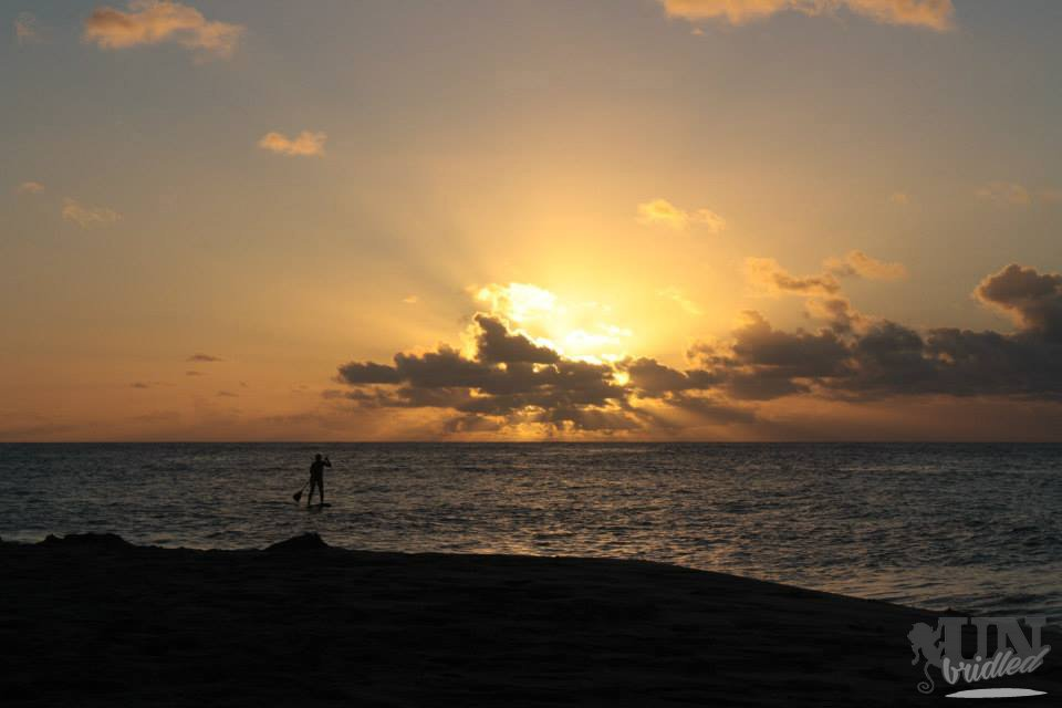 Das Gefühl von Freiheit, wenn man einem Stand-up-Paddler dabei beobachtet, wie er hinaus aufs Meer paddelt und dabei die Sonne in orangen Farben untergeht.