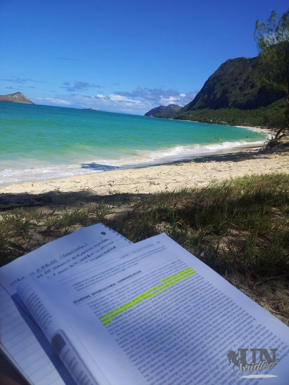 Mit Büchern am Strand lernen, Berge im Hintergrund, blaues Meer