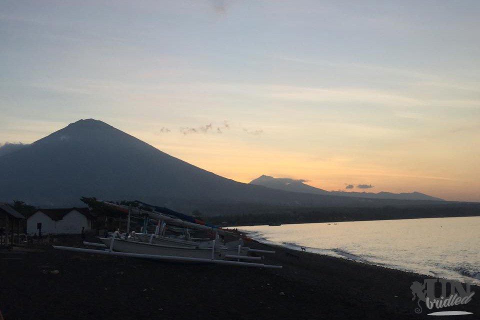 Beaches in Bali: black beach with boats and a volcano in the background