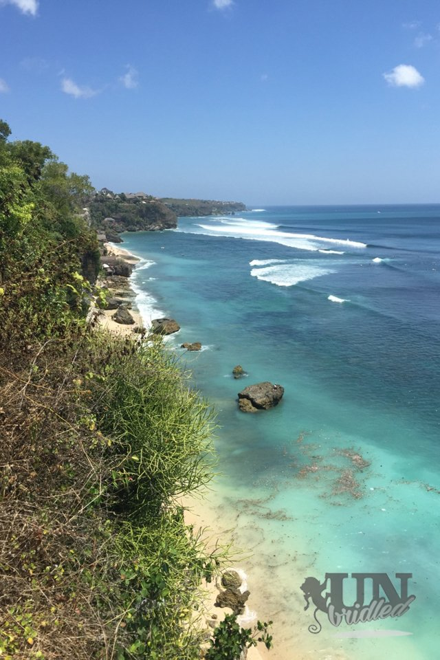 Beaches in Bali: view on the Bingin beach from a above, small white beach stripe with black rocks, blue water