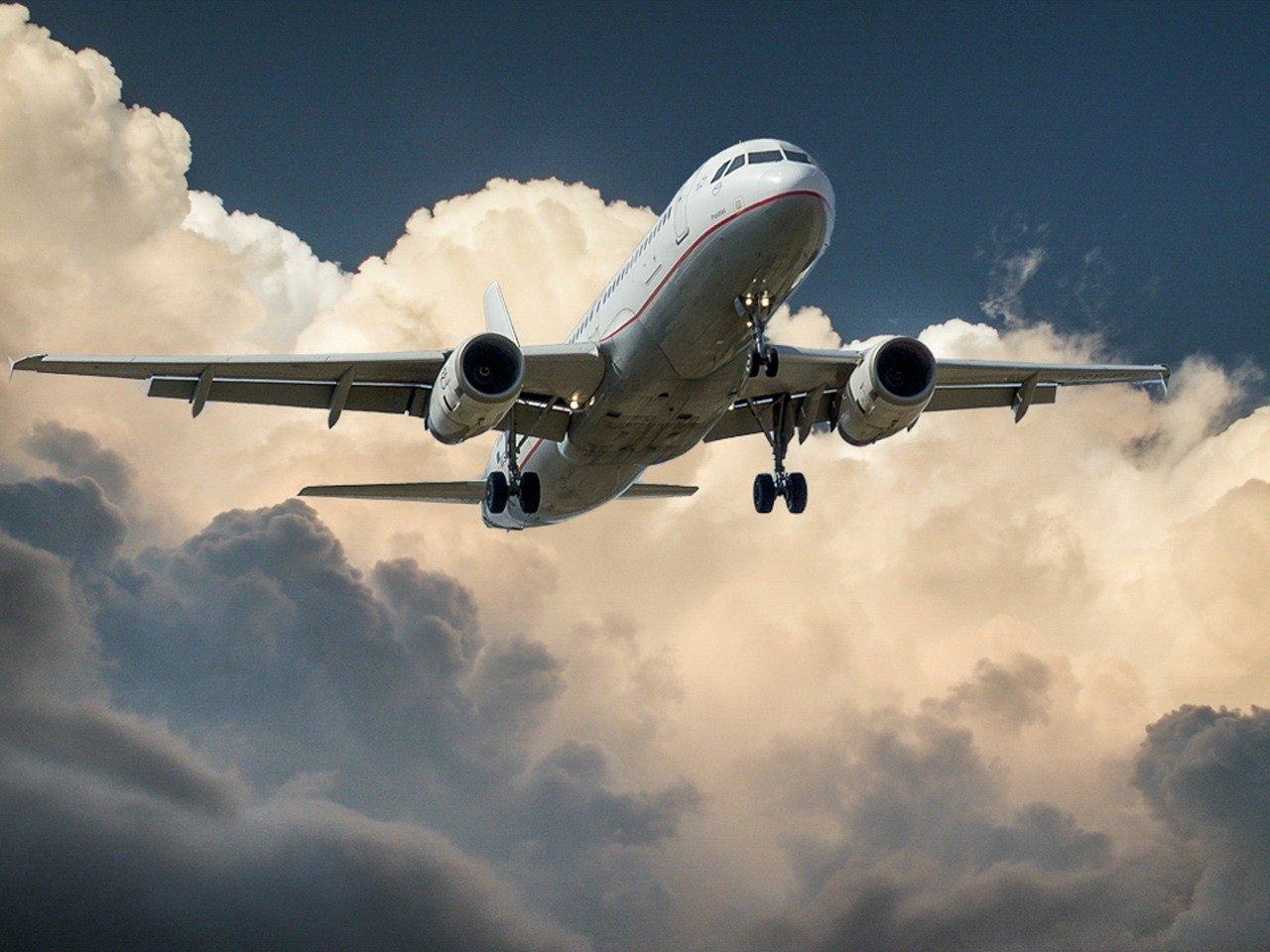 Studium abbrechen und im Flieger sitzen: Flugzeug beim Start am Himmel, Wolken im Hintergrund