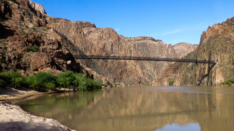 Kaibab Trail: See am Grunde des Gran Canyon mit einer schwarzen Brücke von einer Felswand zur anderen