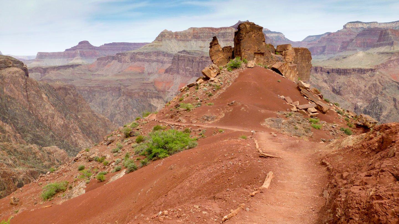 Kaibab Trail: So rote Erde, dass man meint, man wäre auf dem Mars, kaum Vegetation, nur Felsbrocken und Sand