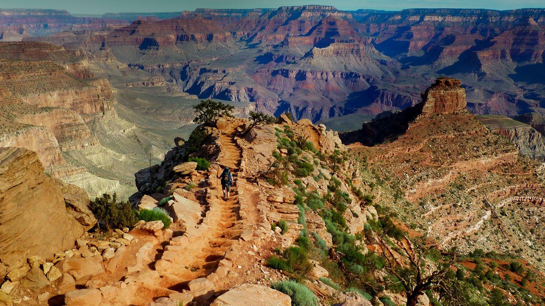Stufen auf der Ridge hinein in den Grand Canyon, grüne Büschlein zieren die rot-orangen Gesteine