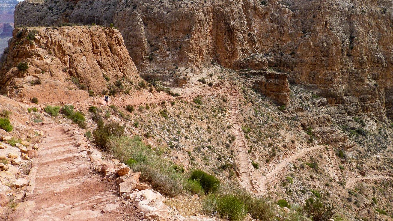 Kaibab Trail: Switchbacks führen zickzack-mäßig in den Grund des Gran Canyons, nur Gestein und ein paar Büsche