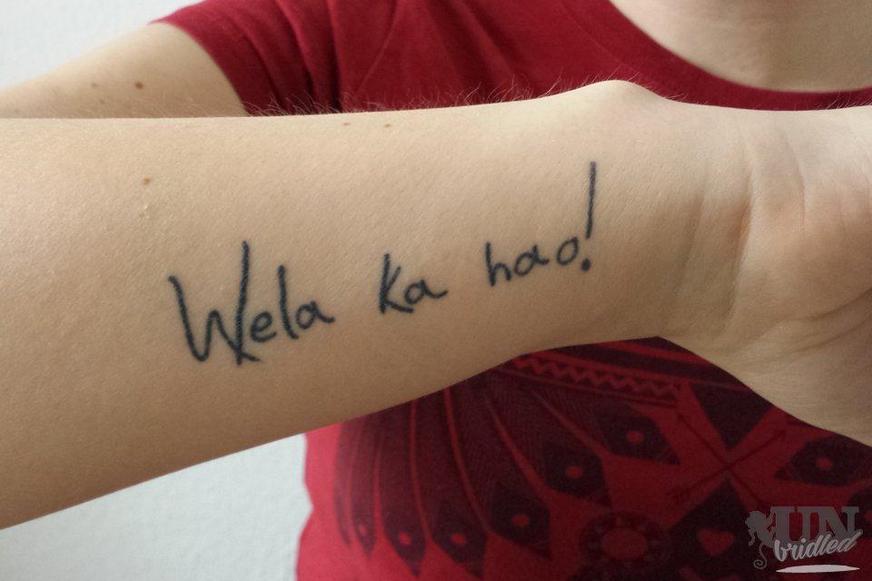"""drop out study: forearm tattoo says """"Wela ka hao!"""""""