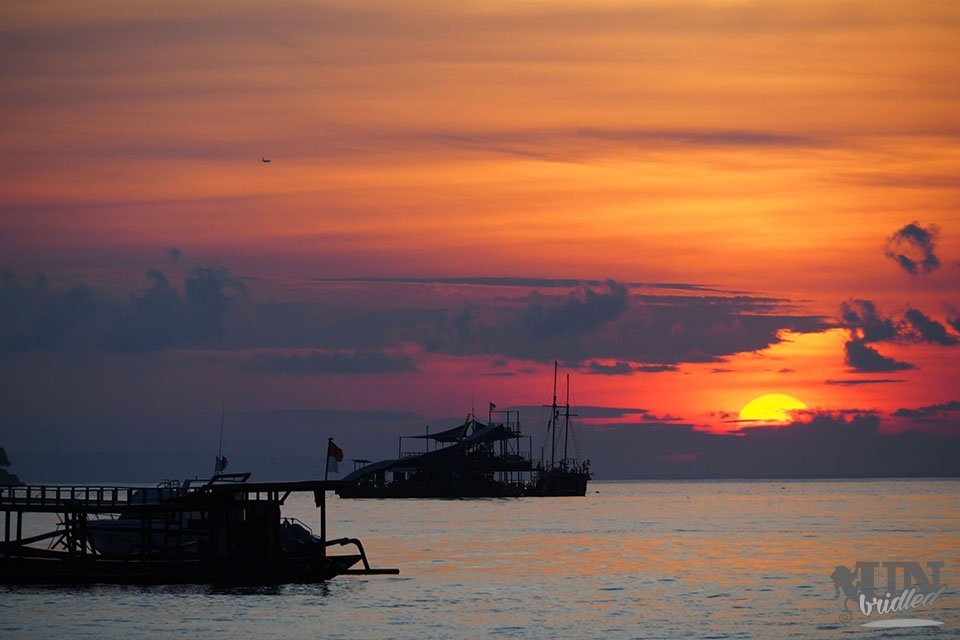 Boats on the ocean in front of Nusa Lembongan at sunset