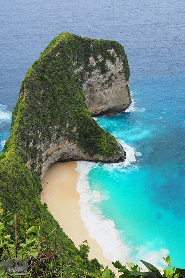 Secluded white-sand beach in the cove of an limestone arm, that goes into the blue ocean