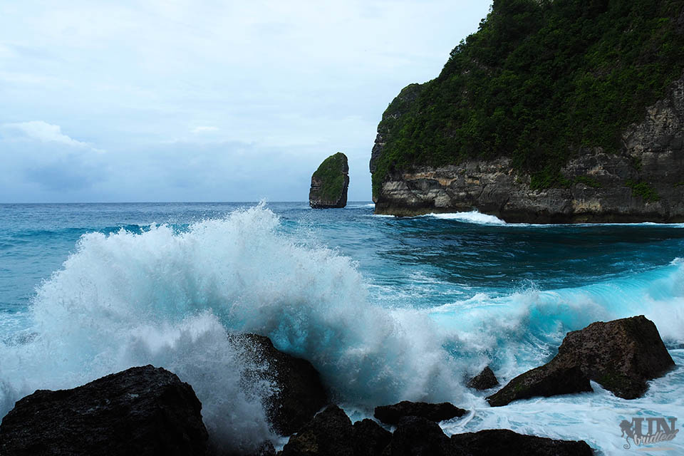 Big wave crashes into rock. In the background is the blue ocean and the coastal rock formations of Nusa Penida