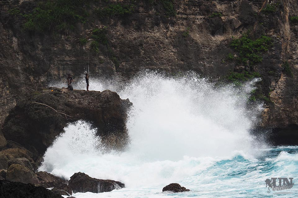 Big wave crashes into a huge rock, where fishermen stand on top