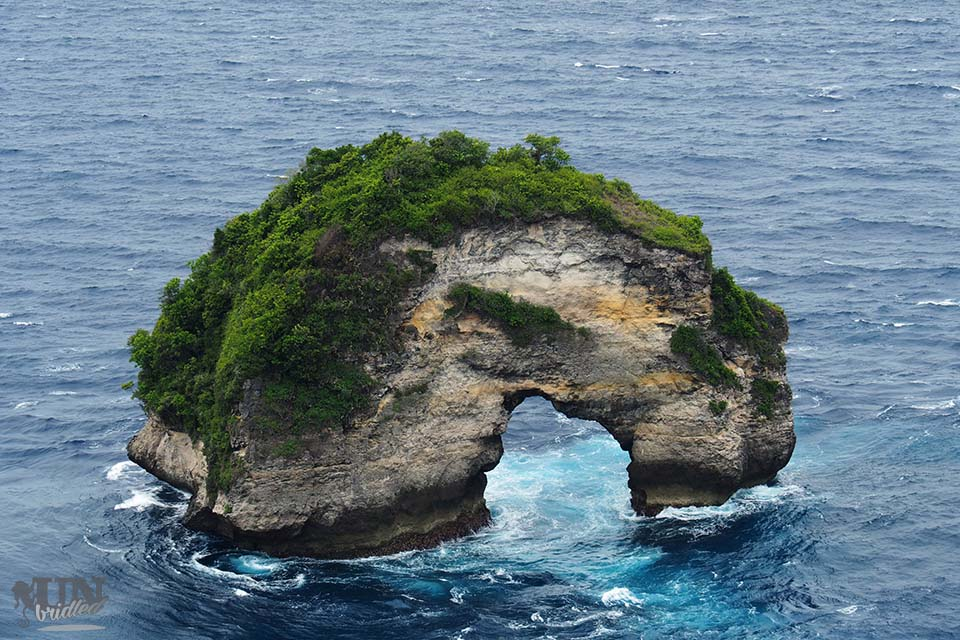 Stone arche in the blue ocean in front of Nusa Penida