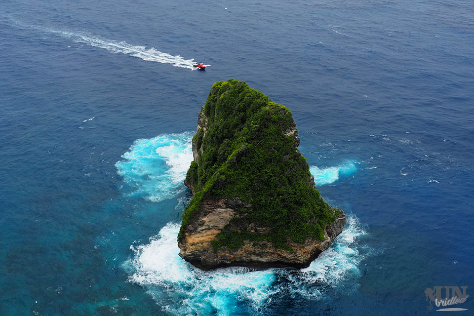 Rock formation and a red boat in front of Nusa Penida
