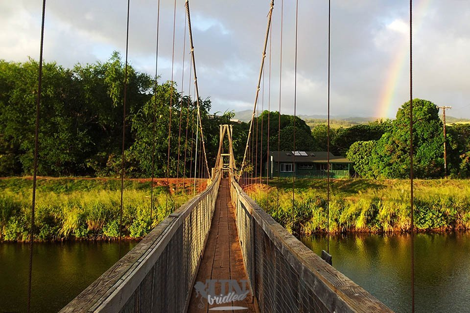 Hanging bridge at sunset with a rainbow