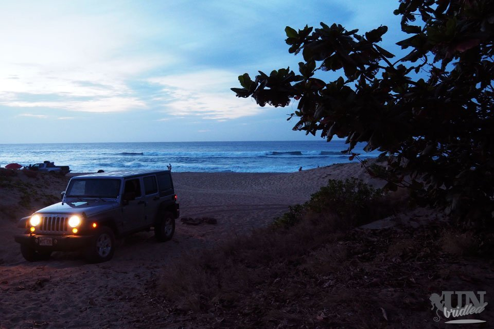 Rental car parked in the dunes of a beach for an over-night stay to do Kauai on a budget