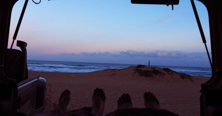 Visiting Kauai on a budget has benefits: View from the car onto the ocean and beach at sunrise