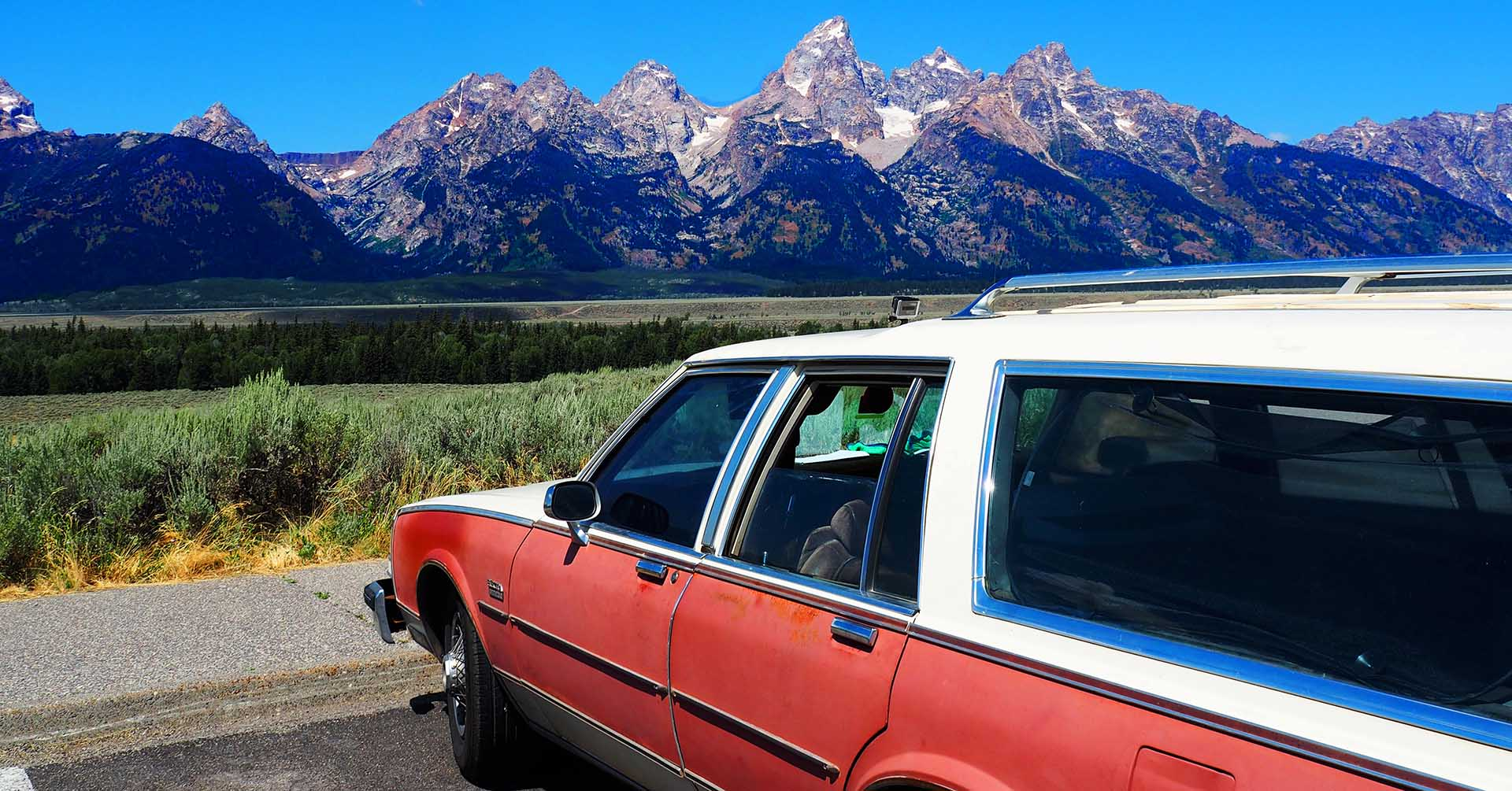 Old car in front of montains as an inspiration or planning a road trip