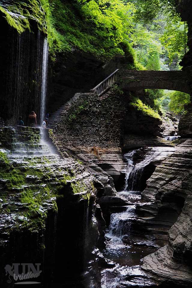Kleiner Wasserfall über dem Wanderpfad und Brücke über dem Fluss im Watkins Glen State Park