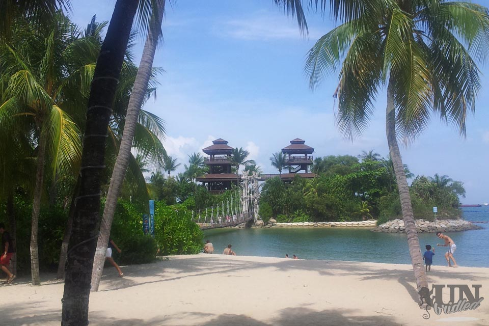Singapore's fake beach, palm trees, hanging bridge to a little island with two towers