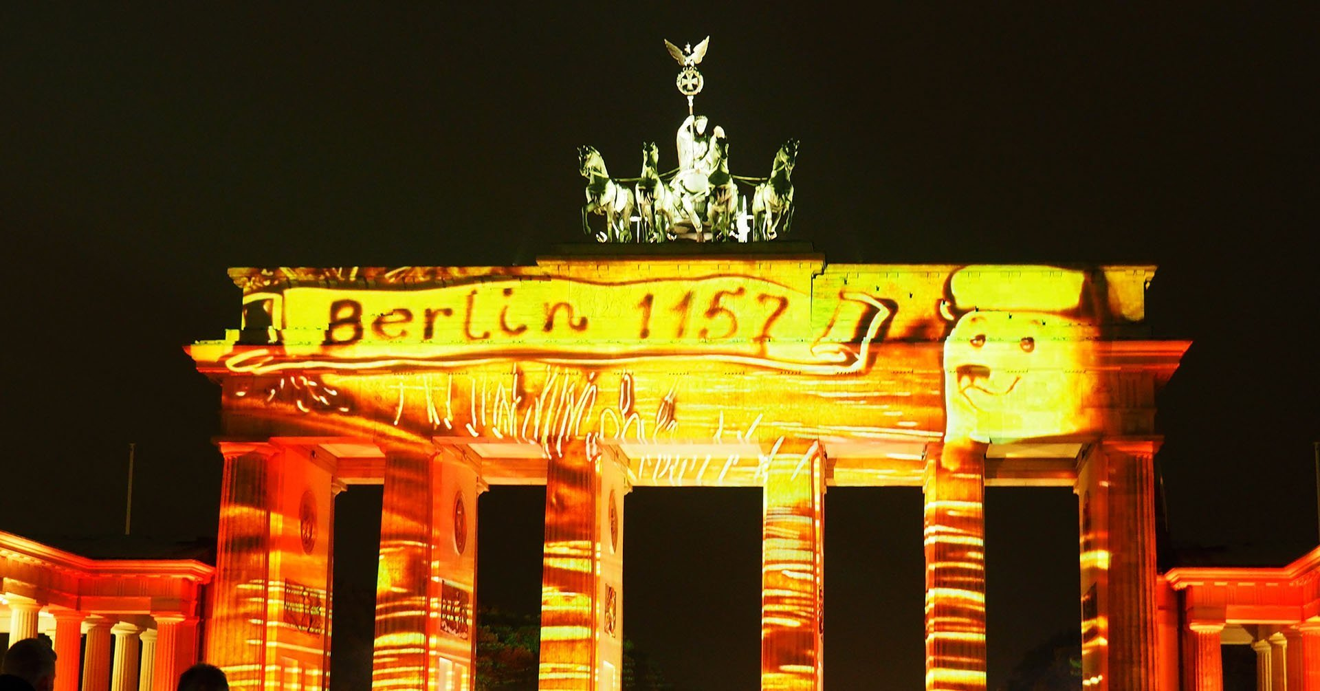 Berlin Gate illuminated in yellow tones during Festival of Lights