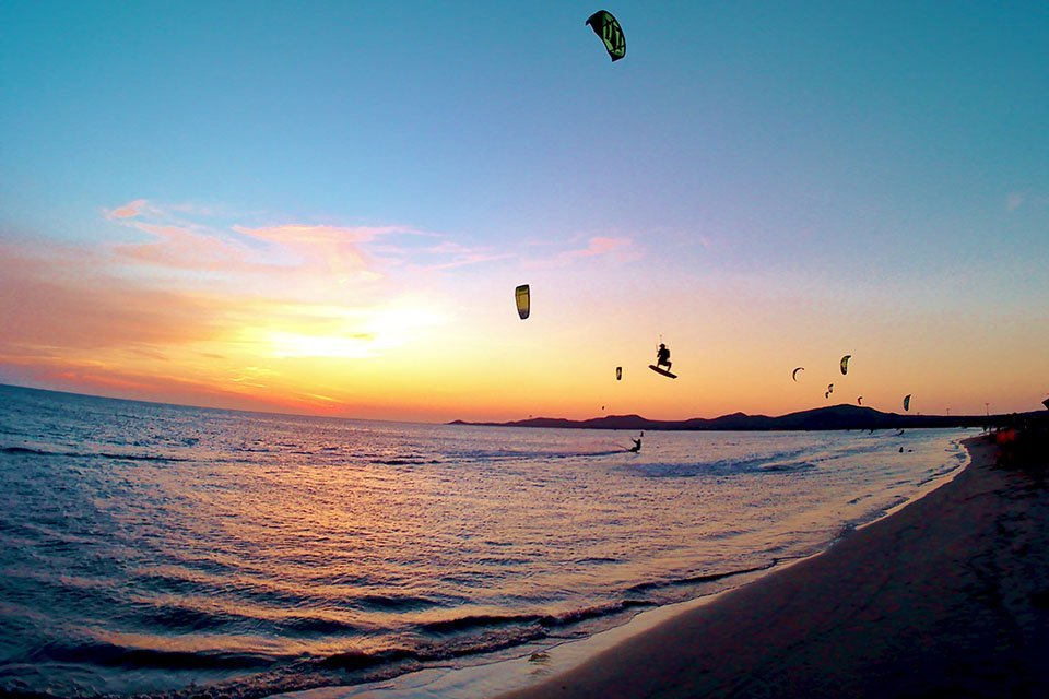Sunset scene at the coast in Columbia with kite surfers