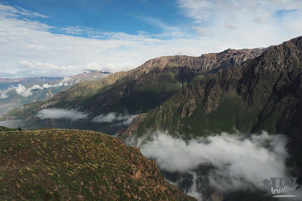 Tal und Berge des Colca Canyon (Peru) mit flauschigen Wolken in der Schlucht