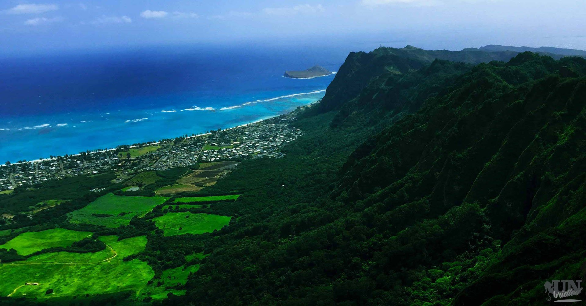 The spread mountain range behind the Waimanalo beach is covered in green