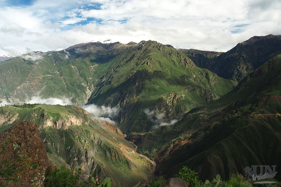 Green mountains with clouds and the river at the bottom of the Colca Canyon