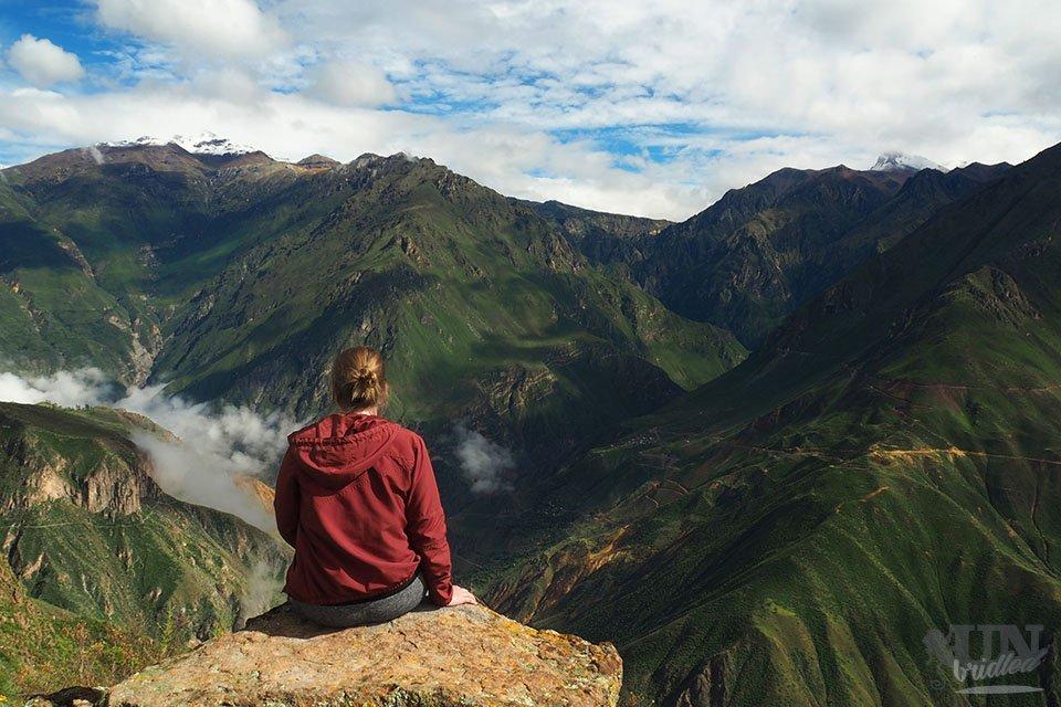 Frau mit roter Jacke sitzt auf einem Felsen mit den grünen Bergen und fluffigen Wolken des Colca Canyons in Peru vor sich