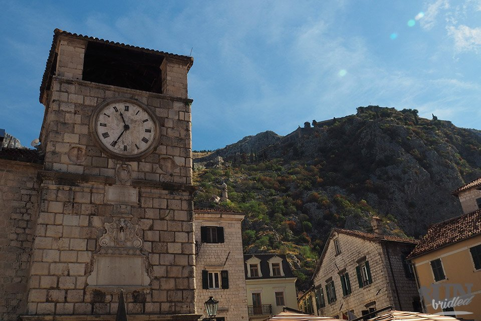 Old clock tower in Kotor in Mediterranean style with mountains and more buildings in the background