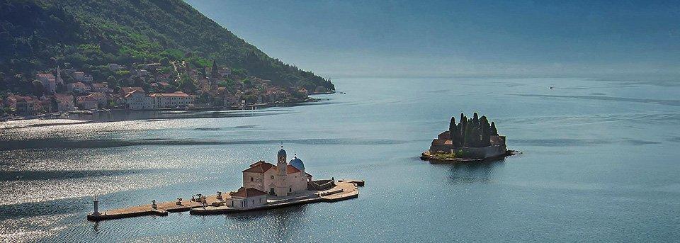 Zwei Inseln in der Bucht von Kotor mit Kirchen. Im Hintergrund liegt eine andere Altstadt namens Perast