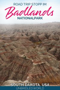 Braune Hügel des Badlands Nationalparks in den USA mit dem Text: Road Trip Stopp im Badlands Nationalpark