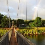Bridge at sunset with a rainbow in the background and the text: Kauai on a budget
