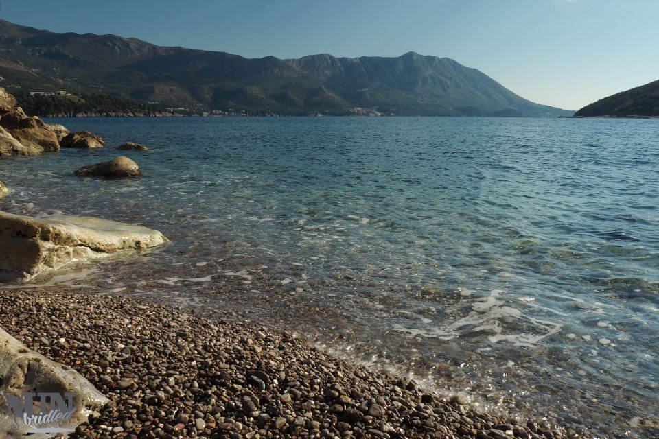 Pebble beach with crystal-clear water and mountains in the backgorund in Montenegro