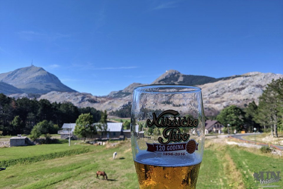 Beer glass in front of mountainous scenery at Lovcen National Park