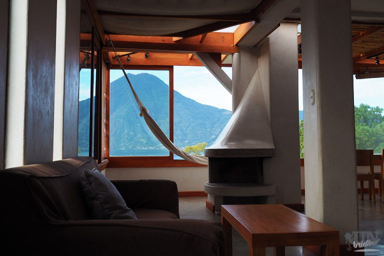 Living room with a couch, fireplace, hammock and table with a scenic view of Lake Atitlan out of the window