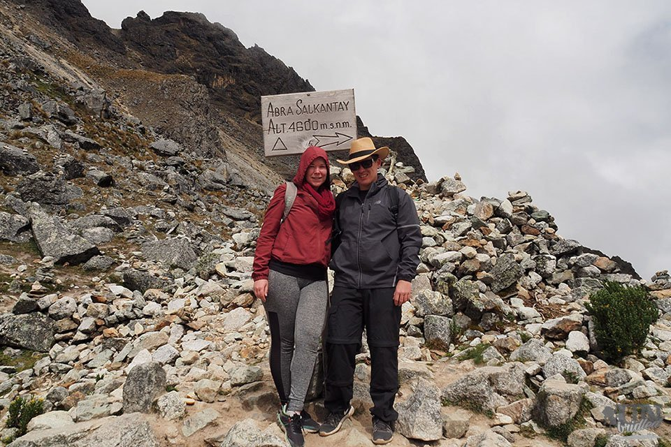 Woman and man in front of a trail sign at the Salkantay Pass