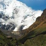 Camp mit einem riesigen schneebedeckten Berg im Hintergrund und dem Text: Salkantay Trek - Ein Abenteuer zum Machu Picchu
