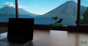 Laptop auf einem Tisch, von wo man eine Aussicht auf die Berge und den See hat
