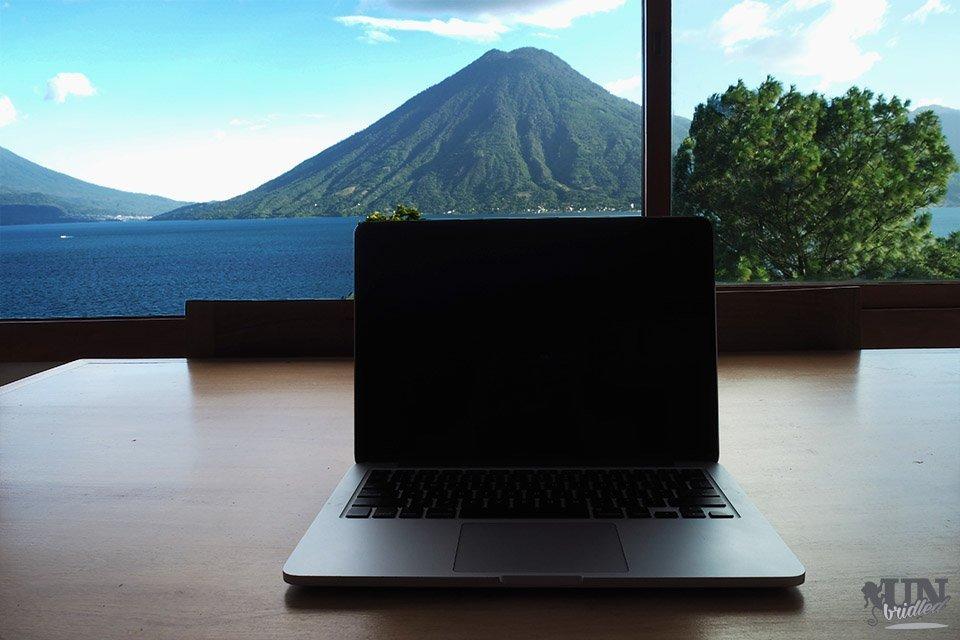 Laptop auf einem Tisch vor einem großen Fenster mit dem Ausblick auf den Atitlan-See in Guatemala