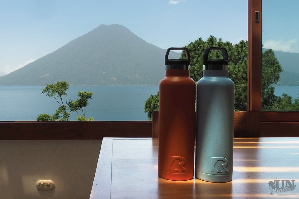An orange and a blue Rtic bottle on a table with a scenic background