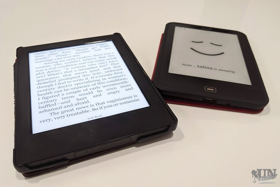 Two black ebook readers on a white surface