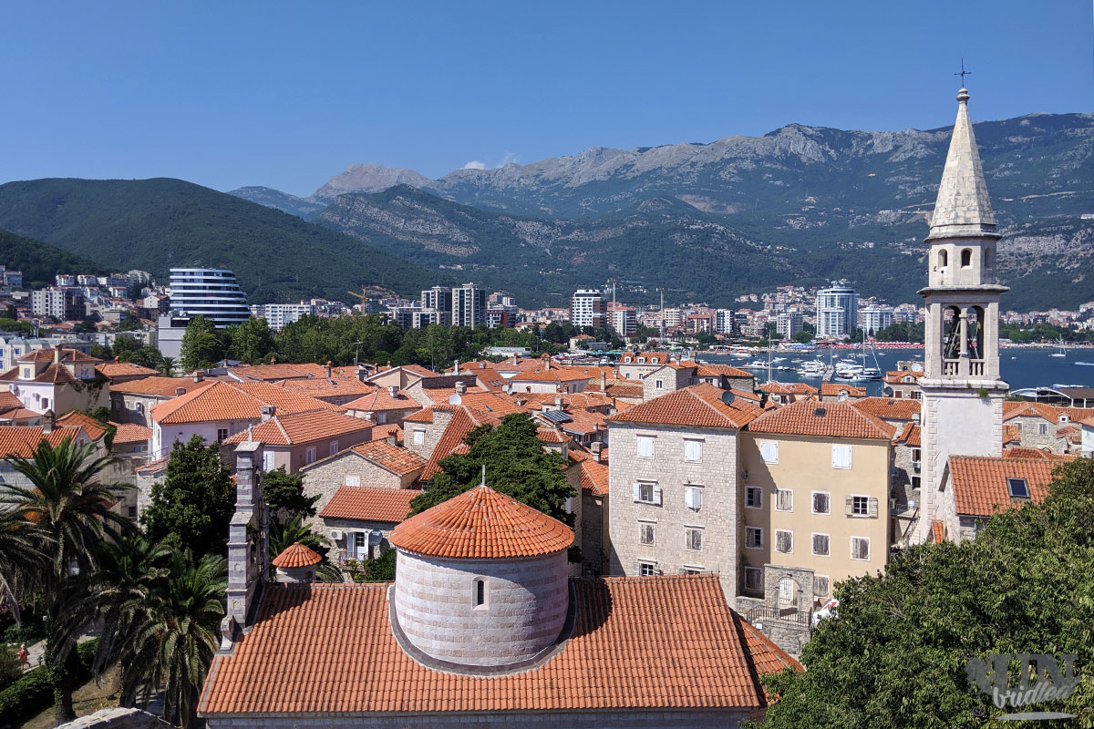 Foto aufgenommen über den roten Dächern von Budva, es zeigt die Kirchen und die bergige Landschaft