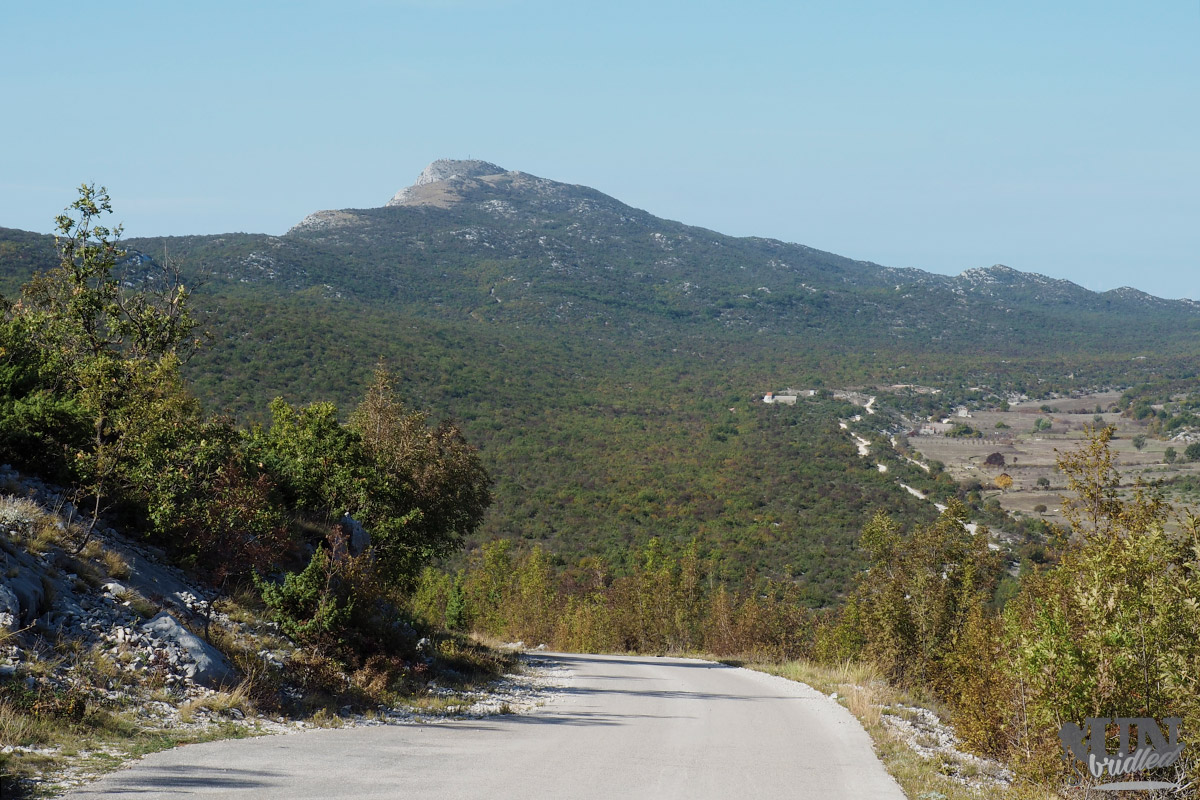 Asphalt street leading to Kozjak mountain with green scenery